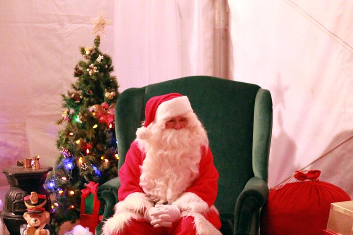"""סנטה קלאוס באוהל הבזאר ביריד אורות החורף של אירדרי. הילדים עומדים יפה בתור, אח""""כ יושבים בחיקו ומבקשים מתנות. ממש כמו בסרטים.אנקדוטה משעשעת - אנחנו מכירים מישהו שנראה כמו סנטה באמת, והוא פעם היה עושה סנטה, אבל נמאס לו שילדים מושכים לו בזקן כי הם בטוחים שהוא מזוייף, אז הוא הפסיק."""