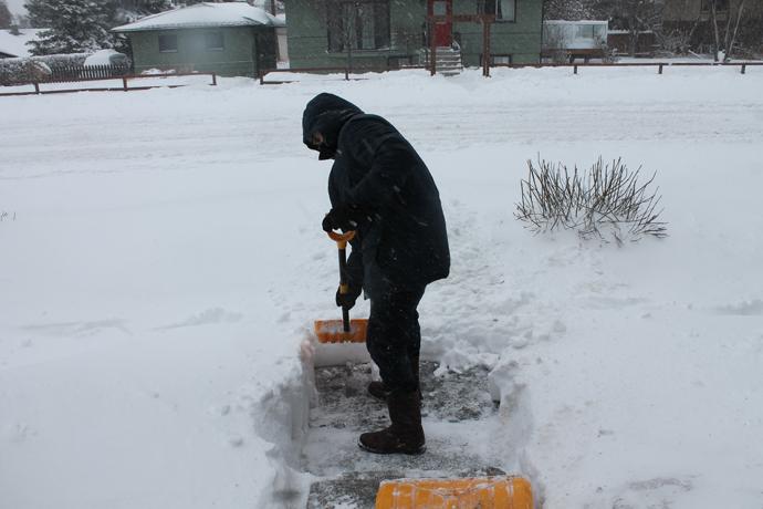 """עופר מפנה שלג אחרי הסופה הגדולה. תראו כמה זה עמוק! לקלגרי זה יוצא דופן. במזרח קנדה יש מקומות שהבית נקבר כ""""כ עמוק, שאתה פותח את הדלת ומעבר לה יש קיר של שלג עד למעלה, ובו טבועה תמונת מראה של הדלת שלך."""