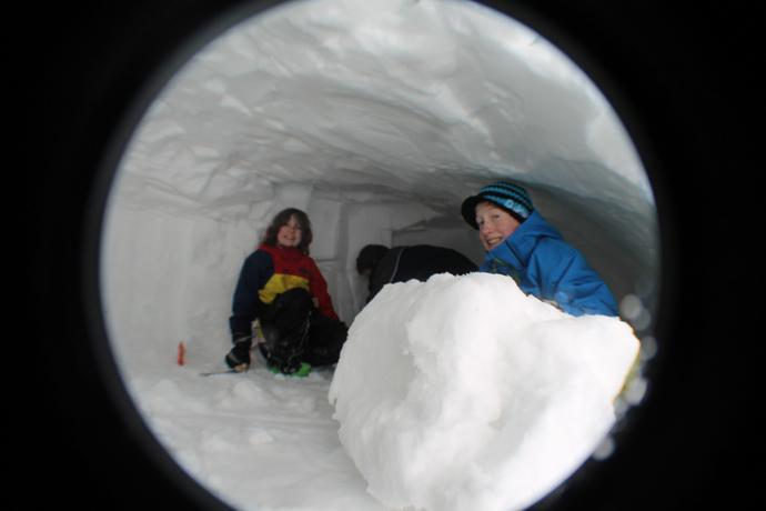 מערת שלג בשלבי חציבה מתקדמים - ילדי המשפחה מגלגלים גושי שלג החוצה